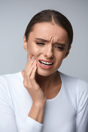 a tooth are beautiful: Tooth Pain And Dentistry. Beautiful Young Woman Suffering From Terrible Strong Teeth Pain, Touching Cheek With Hand. Female Feeling Painful Toothache. Dental Care And Health Concept. High Resolution