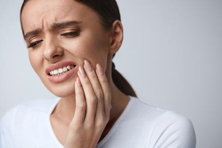 歯の痛み、歯科。美しい若い女性の手で頬に触れて、ひどい強い歯の痛みに苦しんでいます。歯痛の痛み女性の感じ。歯科医療と医療の概念。高分