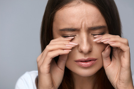Eyes Pain. Beautiful Unhappy Woman Suffering From Strong Eye Pain. Closeup Portrait Of Sad Female Feeling Stress, Touching Tired Painful Eyes With Hands. Health Care, Medical Concept. High Resolution