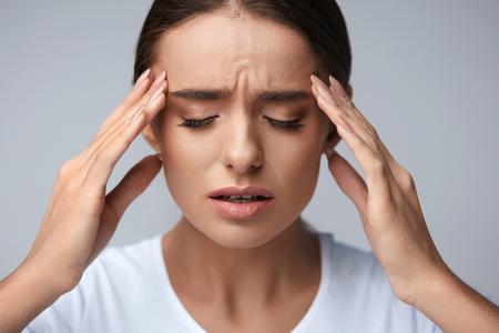 Saúde e Dor. Jovem mulher esgotada forçada que tem a dor de cabeça de tensão forte. Retrato do close up da menina doente bonita que sofre da enxaqueca principal, da pressão do sentimento e do esforço. Imagem de alta resolução
