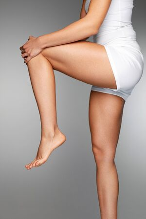 Woman Body Part. Closeup Of Beautiful Female Hands Holding Her Long Slender Leg. Close-up Of Girl Stretching Legs, Touching Painful Knee And Feeling Pain In Knee. Health Care Concept. High Resolution Stock Photo