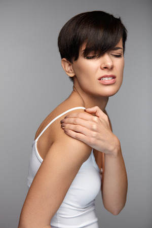 Body Pain. Beautiful Young Woman Feeling Pain In Shoulders. Portrait Of Female Suffering From Painful Feeling In Arms, Touching With Hand Her Injured Shoulder. Health Issues Concept. High Resolution