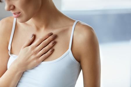 dolor de pecho: Cuidado de la salud del corazón. Primer de la mujer joven que se siente un fuerte dolor en el pecho. Primer Del cuerpo femenino con la mano en el pecho. Mujeres que sufren de sensación dolorosa, Tener problemas de salud. Imagen de alta resolución