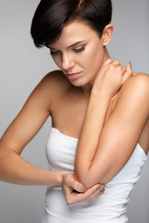Body Pain. Woman Feeling Sharp Pain In Elbows. Portrait Of Beautiful Young Female Suffering From Painful Feeling In Arms, Holding Her Elbow With Hand. Arm Injury, Health Issue Concept. High Resolution
