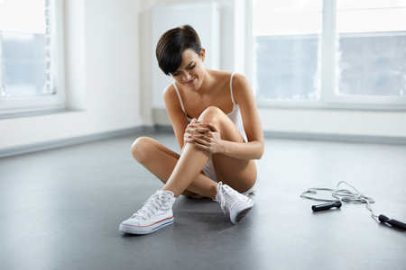 Sports Injury. Beautiful Woman Feeling Pain In Knee, Sitting On Floor And Touching Painful Knee. Girl Injured Her Leg During Sport Workout Indoors. Female Suffering From Pain In Joint. High Resolution