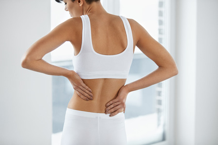 Health Issues. Closeup Of Beautiful Young Woman Having Backache, Strong Back Pain. Female Suffering From Painful Feeling In Muscles, Holding Hands On Her Body. Health Care Concept. High Resolution
