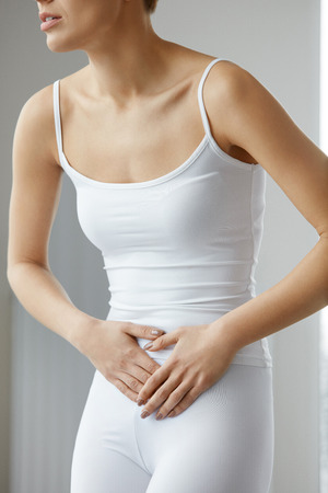 digestion: Health Issues. Beautiful Young Woman Feeling Strong Pain In Stomach. Female Suffering From Painful Feeling, Stomach Ache, Abdominal Pain, Having Digestion Problem. Health Care Concept. High Resolution