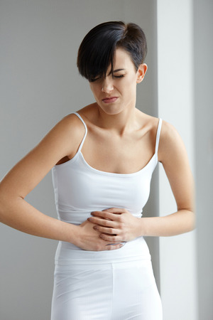 Pain In Stomach. Beautiful Young Woman Feeling Strong Abdominal Pain. Attractive Female Suffering From Painful Stomach Ache, Holding Hand On Belly. Digestion, Health Issues Concept. High Resolution Stock Photo