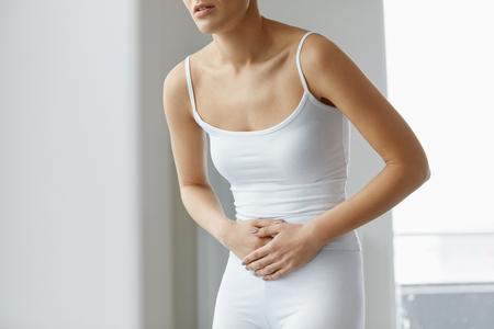 Lichaamspijn. Close-up van het lichaam van het mooie vrouw met sterke buikpijn. Vrouwelijke lijden van pijnlijke gevoel in maag, maag ache, handen op buik vasthouden. Health Issue Concept. Hoge resolutie