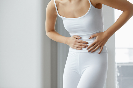 Female Pain. Closeup Of Beautiful Woman Body Feeling Abdominal Pain. Girl With Fit Body Suffering From Painful Stomach Ache, Holding Hands On Belly. Health Issue, Healthcare Concept. High Resolution Stock Photo - 69605111