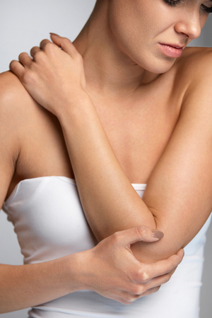 Elbow Pain. Closeup Of Beautiful Womans Body Suffering From Sharp Pain In Elbows. Female Having Painful Feeling In Arms, Touching Arm With Hand. Joint Illness And Arm Injury Concept. High Resolution