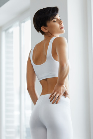 health woman: Back Pain. Beautiful Young Woman Feeling Strong Spinal Pain, Having Health Issue. Attractive Girl Suffering From Painful Feeling, Backache, Holding Hands On Body. Health Care Concept. High Resolution