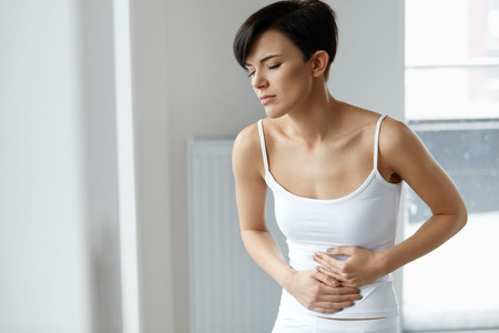 Pain In Stomach. Beautiful Young Woman Feeling Strong Abdominal Pain. Attractive Female Suffering From Painful Stomach Ache, Holding Hand On Belly. Digestion, Health Issues Concept. High Resolution Stockfoto