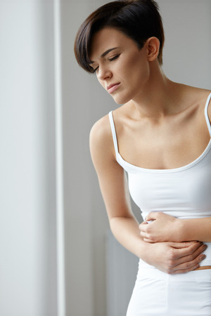digestion: Pain In Stomach. Beautiful Young Woman Feeling Strong Abdominal Pain. Attractive Female Suffering From Painful Stomach Ache, Holding Hand On Belly. Digestion, Health Issues Concept. High Resolution Stock Photo