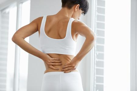 背中の痛み。脊髄を持つ美しい女性や腎臓の痛み、背中の痛みのクローズ アップ。女性の痛みを伴う感覚、筋肉や神経の痛みに苦しんで、体に手を
