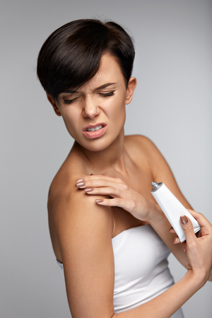 Arm Pain And Injury Treatment. Closeup Of Beautiful Woman Feeling Muscle Or Joint Pain In Shoulders, Applying Medical Cream. Female With Painful Feeling In Body. Health Issues Concept. High Resolution