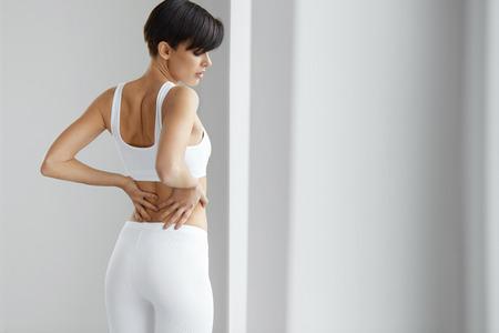 脊髄の痛み。女性の切ない感情、腰痛や腎臓の痛みに苦しんで、体に手を繋いでいます。美しい若い女性腰痛を感じ、健康上の問題を有するします