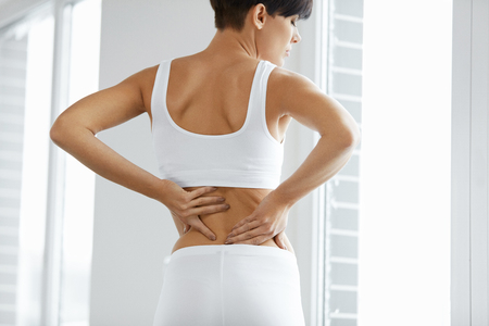 Back Pain. Closeup Of Beautiful Woman Having Spinal Or Kidney Pain, Backache. Female Suffering From Painful Feeling, Muscle Or Nerve Pain, Holding Hands On Body. Health Issue Concept. High Resolution