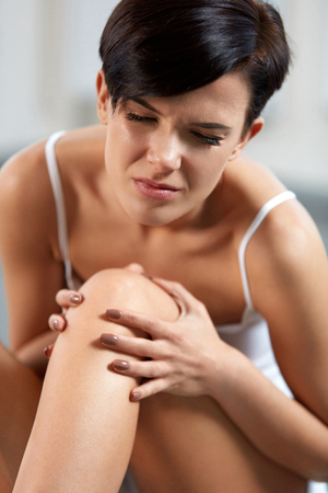 Body Pain. Closeup Of Beautiful Woman With Painful Knee, Feeling Joint Pain. Attractive Young Female Having Health Issues, Sitting On Floor And Touching Her Leg. Health Care Concept. High Resolution Stock Photo