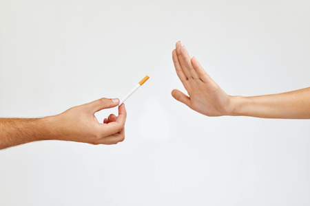 Anti Smoking. Closeup Of Beautiful Woman Hand Refusing To Take Cigarette From Another Hand. Human Hands Holding Cigarette On White Background. Quit Smoking Concept. High Resolution