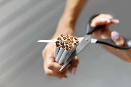 them: Quit Smoking. Closeup Of Beautiful Woman Hands Holding Bunch Of Cigarettes And Cutting Them With Scissors. Female Hands Cuts Cigarettes In Halves With Scissors, Quitting Smoking. High Resolution