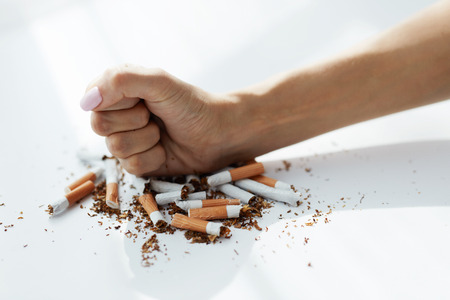 bad habit: Healthy Lifestyle. Closeup Of Woman Fist Breaking Many Cigarettes On White Background. Female Stops Smoking By Hitting Lots Of Cigarettes With Hand. Quitting Bad Habit. High Resolution