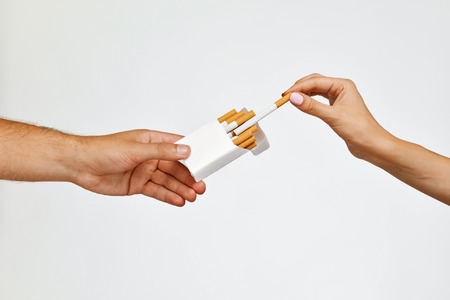 cigarette pack: Smoking Cigarettes. Closeup Male Hand Holding Cigarette Pack, Proposing It To Woman. Close-up Female Hand Taking Cigarette From Package On White Background. Nicotine Addiction Concept. High Resolution