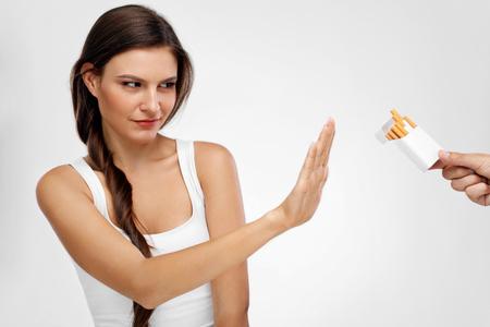 健康的なライフ スタイル。美しい若い女性タバコにノーという、禁煙の肖像画。クローズ アップ女性がタバコを吸って停止手の兆しを拒否します。