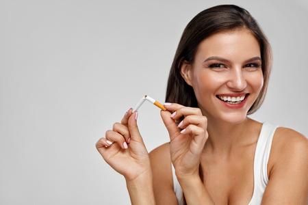 Dejar de fumar cigarrillos. Retrato de la mujer sonriente dejar de fumar mediante la ruptura del cigarrillo. Primer de la muchacha feliz celebración de cigarrillos roto en las manos. Concepto de salud. Alta resolución Foto de archivo