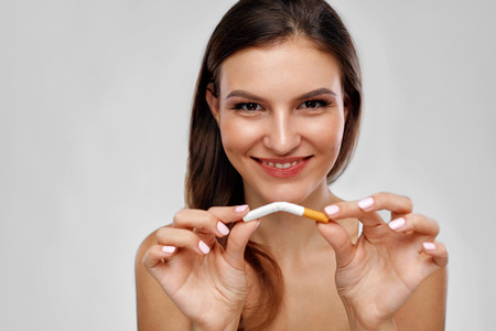 Stop Smoking. Closeup Of Beautiful Happy Woman Holding Cigarette, Quitting To Smoke Cigarettes. Portrait Of Smiling Young Female Breaking Cigarette In Half. Bad Habit Concept. High Resolution