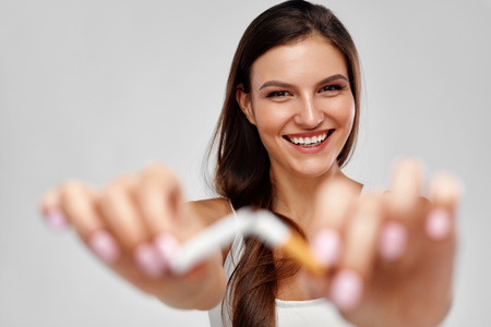 Healthy Lifestyle. Closeup Beautiful Happy Female Quitting To Smoke, Holding Broken Cigarette In Hands. Portrait Of Smiling Woman Breaking Cigarette. Quit Smoking, Bad Habit Concept. High Resolution