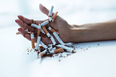 Quit Smoking Cigarettes. Closeup Of Beautiful Woman Hand Holding Lots Of Cigarettes. Close-up Of Female Hand Breaking Cigarettes,  Quitting Smoking. Stop Nicotine Addiction Concept. High Resolution
