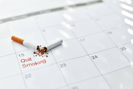 Quit Smoking Cigarettes. Closeup Of Broken Cigarette Lying On Month Calendar, Certain Date Marked As Quit Day. Stop To Smoke Cigarettes, Anti-Smoking Concepts. High Resolution