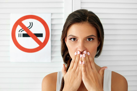 No Smoking. Portrait Of Beautiful Young Woman Holding Hand Near Mouth With Anti-Smoking Sign On Background. Closeup Of Healthy Girl Quitting To Smoke Cigarettes. Non-Smoking Concept. High Resolution Stock Photo