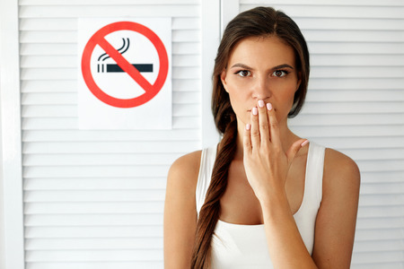 young lady: No Smoking. Portrait Of Beautiful Young Woman Holding Hand Near Mouth With Anti-Smoking Sign On Background. Closeup Of Healthy Girl Quitting To Smoke Cigarettes. Non-Smoking Concept. High Resolution Stock Photo