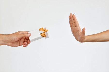 Quit Smoking. Closeup Of Beautiful Woman Hand Refusing To Take Cigarettes From Pack On White Background. Human Hand Gestures No Sing To Cigarette Package. Quitting Bad Habit Concept. High Resolution