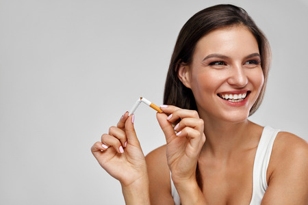 Quit Smoking Cigarettes. Portrait Of Beautiful Smiling Woman Quitting Smoking By Breaking Cigarette. Closeup Of Happy Girl Holding Broken Cigarette In Hands. Health Care Concept. High Resolution Stock Photo