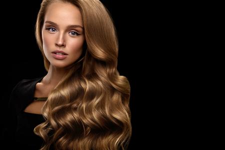 Hair Beauty und Make-up. Schöne Mode Mädchen Modell mit perfekter Blonder Haarfarbe und herrlichem Gesicht. Attraktive reizvolle Frau mit dem gesunden langen Glänzende wellenförmigen lockigen Haar posiert in Studio. Hohe Auflösung