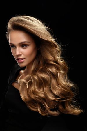 Piękne długie włosy. Moda modelka z piękna twarzy makijaż i Zdrowe Shiny Blonde Falista kręcone włosy na czarnym tle. Portret kobiety z pięknym fryzurę i kolor włosów. Wysoka jakość Zdjęcie Seryjne