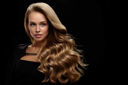 Hair Beauty und Make-up. Schöne Mode Mädchen Modell mit perfekter Blonder Haarfarbe und herrlichem Gesicht. Attraktive reizvolle Frau mit dem gesunden langen Glänzende wellenförmigen lockigen Haar posiert in Studio. Hohe Auflösung Standard-Bild