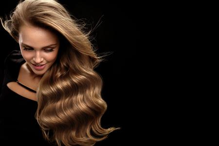 Belle Cheveux longs. Mannequin Femme Avec Beauté Maquillage Et sain Shiny Blonde Wavy cheveux bouclés sur fond noir. Portrait de femme avec superbe coiffure et la couleur des cheveux. Haute qualité Banque d'images