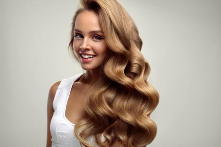 헤어 미용. 흰색 배경에 건강 긴 빛나는 금발 물결 모양의 곱슬 머리를 가진 아름 다운 여자. 완벽한 패션 헤어 스타일로 소녀 모델의 초상화. 미용 및