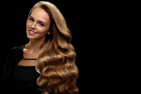 곱슬 금발 머리. 완벽한 메이크업, 화려한 볼륨으로 뷰티 모델 소녀와 검은 색 바탕에 머리카락 색 서입니다. 건강한 긴 빛나는 물결 모양의 머리 초상