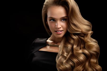 美しい巻き毛。完璧なメイク、ゴージャスなボリュームとブロンドの髪色で女性の美のモデル。黒い背景に健康の長い光沢のあるウェーブのかかっ