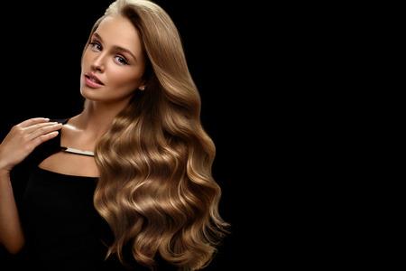 Beauté des cheveux et le maquillage. Belle Mannequin Fille Avec Perfect Blonde Couleur des cheveux et magnifique visage. Femme Sexy attrayant avec sain long Brillant Wavy Cheveux frisés posant en studio. Haute résolution