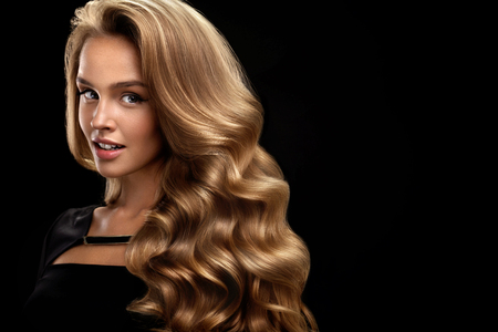 아름다운 곱슬 머리. 완벽한 메이크업, 화려한 볼륨 그리고 금발 머리 색상으로 여성의 아름다움 모델. 검은 색 바탕에 건강한 긴 빛나는 물결 모양의  스톡 콘텐츠