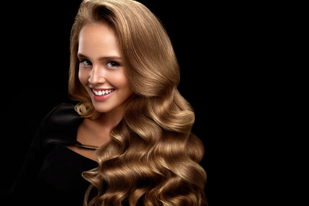 black: Hairstyle. Beautiful Woman With Healthy Long Shiny Blonde Wavy Curly Hair On Black Background. Portrait Of Smiling Girl Model With Nice Face Makeup Perfect Curls. Hair Beauty Concept. High Resolution