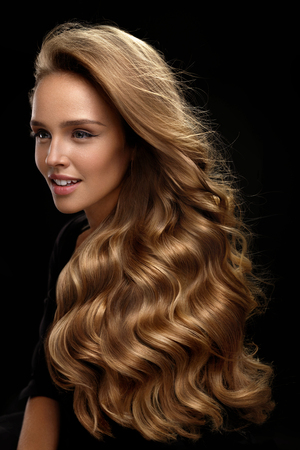 Beautiful Long Hair. Fashion Female Model With Beauty Face Makeup And Healthy Shiny Blonde Wavy Curly Hair On Black Background. Portrait Of Woman With Gorgeous Hairstyle And Hair Color. High Quality Stockfoto