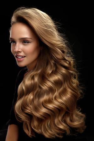 Schönes langes Haar. Mode weibliche Modell mit Schönheit Gesicht Make-up und gesunde Shiny Blonde Wellenförmige lockige Haare auf schwarzem Hintergrund. Porträt der Frau mit herrlichen Frisur und Haarfarbe. Gute Qualität