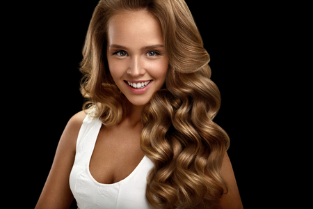 Hairstyle. Beautiful Woman With Healthy Long Shiny Blonde Wavy Curly Hair On Black Background. Portrait Of Smiling Girl Model With Nice Face Makeup Perfect Curls. Hair Beauty Concept. High Resolution